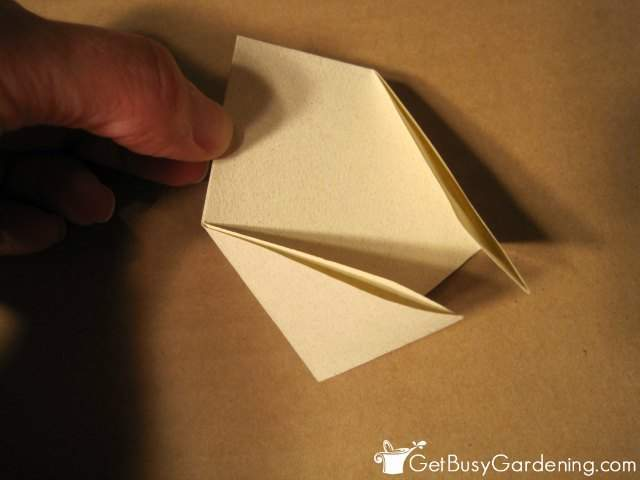 Folding in the two corners to create the envelope design