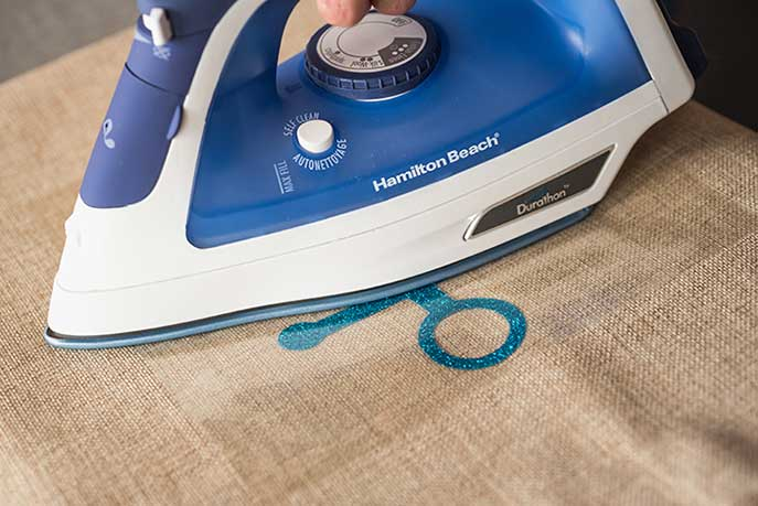 ironing a decal onto synthetic fabric