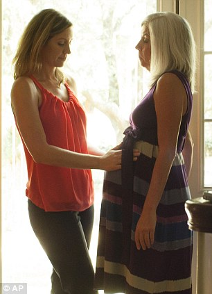 Emily Jordan, left, examines the pregnant belly of her mother Cindy