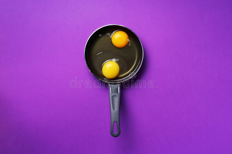 Food concept with two eggs, pan on violet background. Top view. Creative pattern in minimal style. Flat lay. Food concept with two eggs, pan on violet background royalty free stock photography