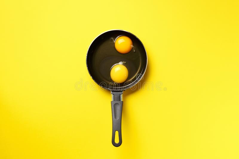 Food concept with two eggs, pan on yellow background. Top view. Creative pattern in minimal style. Flat lay. Food concept with two eggs, pan on yellow background royalty free stock photo