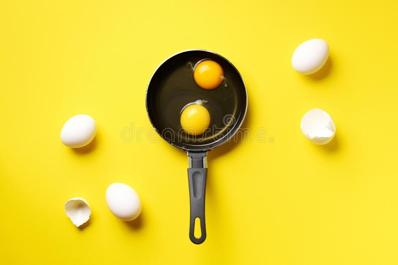 Food concept with two eggs, shells, pan on yellow background. Top view. Creative pattern in minimal style. Flat lay. Food concept with two eggs, shells, pan on royalty free stock photos