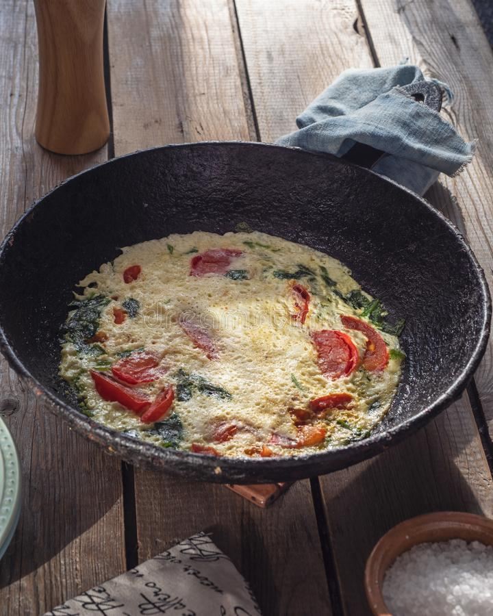 Omelet with tomatoes in a round cast iron pan on an old Board table, a napkin with a pattern and a large salt in a salt. Omelet with tomatoes in a round cast royalty free stock images