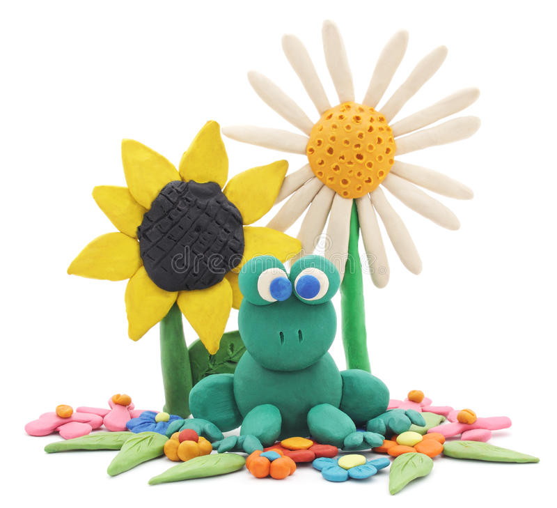 Plasticine frog and flowers. Plasticine frog and flowers on a white background royalty free stock image