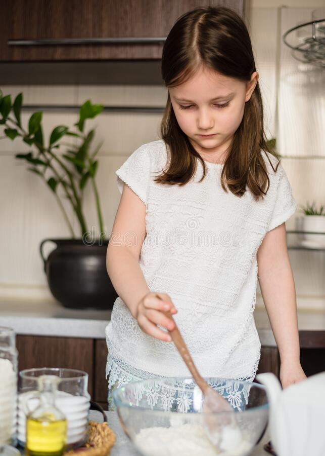 Homemade plastiline. Plasticine. play dough. A preschool girl prepares homemade plasticine from flour, salt and sunflower oil and blue food coloring. The child stock photos