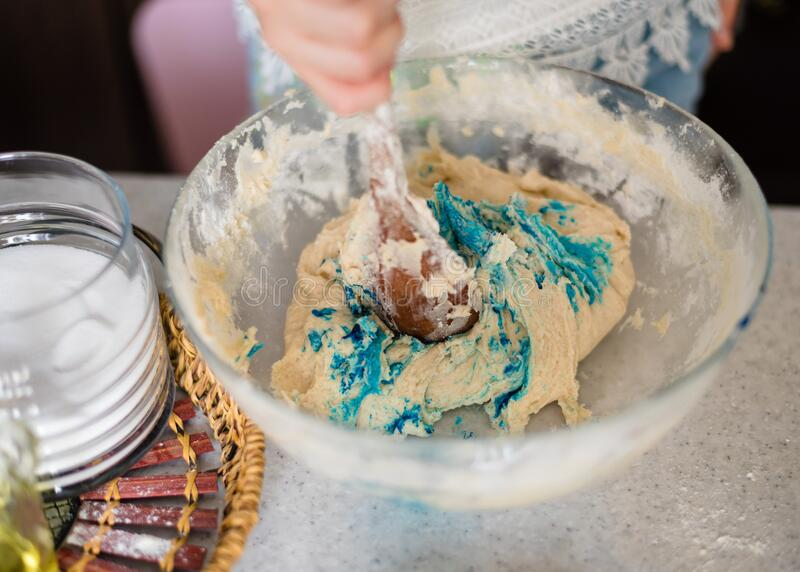 Homemade plastiline. Plasticine. play dough. A preschool girl prepares homemade plasticine from flour, salt and sunflower oil and blue food coloring. The child royalty free stock photo
