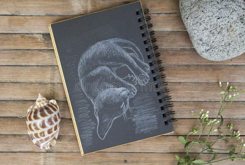 Sleepy kitty hand-drawn illustration. Young cat by white chalk on black paper. Black paper notepad on wooden background. Vintage wooden table with artwork stock image