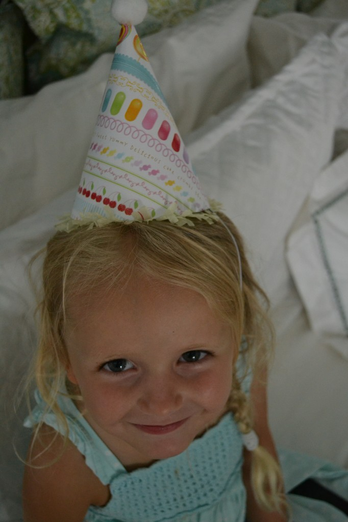 Looking darling in her cute diy paper party hat.